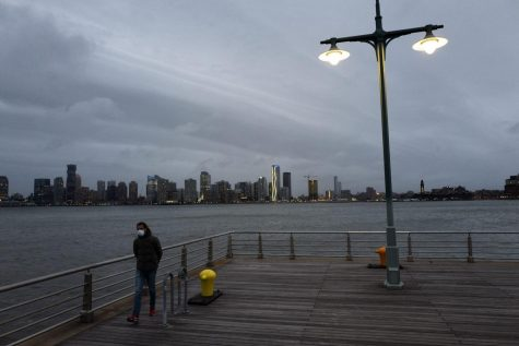 A man wears a face mask as he walks on Pier 45 in Hudson River Park, Thursday night, April 30, 2020, in New York.