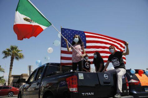 Melany Gamboa, de doce años, sostiene una bandera mexicana mientras su familia sostiene una bandera estadounidense durante un mitin.
