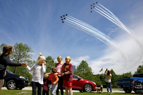 "The Ferry family, from Chantilly, Va., who were in the middle of taking a family photograph, are surprised by a second fly over by the Blue Angels and Thunderbirds, in a ""salute to frontline COVID-19 responders,"" as seen near the U.S. Marine Corps War Memorial that depicts a flag raising over Iwo Jima, in Arlington, Va., Saturday, May 2, 2020."