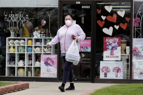 A woman wears mask as she leaves a store during the coronavirus pandemic in Deerfield, Ill., Tuesday, May 5, 2020. New Illinois rules about wearing a face mask over age 2 start Friday, May 1, when they can