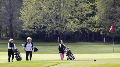 A group of golfers walks with their clubs off a green at the Weston Golf Club, in Weston, Mass., Thursday, May 7, 2020. Golf courses across Massachusetts were allowed to reopen on Thursday, with new social distancing and other health requirements, after they were closed due to the COVID-19 virus outbreak.