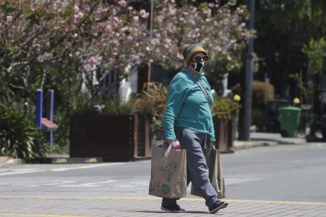 Virginia Nielsen wears a mask while carrying shopping bags during the coronavirus outbreak in San Francisco, Thursday, May 7, 2020.