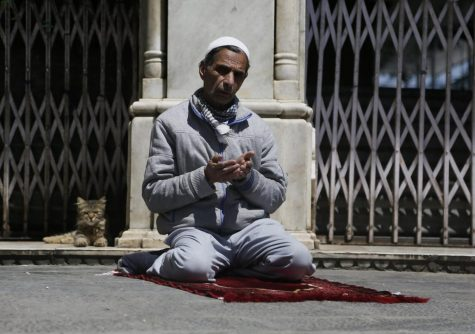 A Kashmiri Muslim prays, as a cat sits next him outside the closed gate of a muslim shrine during the holy fasting month of Ramadan in Srinagar, Indian controlled Kashmir, Friday, May 8, 2020. Religious clerics and authorities in Indian portion of Kashmir have urged people to pray inside their homes to prevent spread of coronavirus in the region. Muslims across the world are observing the holy fasting month of Ramadan, where they refrain from eating, drinking and smoking from dawn to dusk.