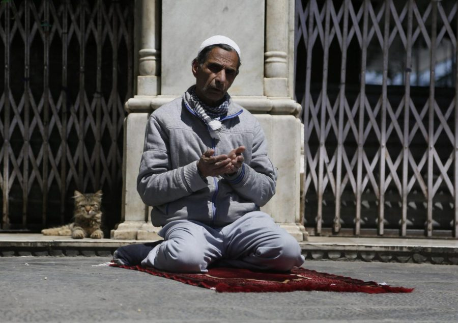 A+Kashmiri+Muslim+prays%2C+as+a+cat+sits+next+him+outside+the+closed+gate+of+a+muslim+shrine+during+the+holy+fasting+month+of+Ramadan+in+Srinagar%2C+Indian+controlled+Kashmir%2C+Friday%2C+May+8%2C+2020.+Religious+clerics+and+authorities+in+Indian+portion+of+Kashmir+have+urged+people+to+pray+inside+their+homes+to+prevent+spread+of+coronavirus+in+the+region.+Muslims+across+the+world+are+observing+the+holy+fasting+month+of+Ramadan%2C+where+they+refrain+from+eating%2C+drinking+and+smoking+from+dawn+to+dusk.+
