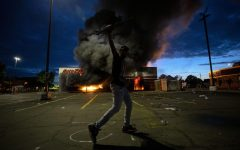 A man poses for a photo in the parking lot of an AutoZone store in flames, while protesters hold a rally for George Floyd in Minneapolis on Wednesday, May 27, 2020. Violent protests over the death of the black man in police custody broke out in Minneapolis for a second straight night Wednesday, with protesters in a standoff with officers outside a police precinct and looting of nearby stores.
