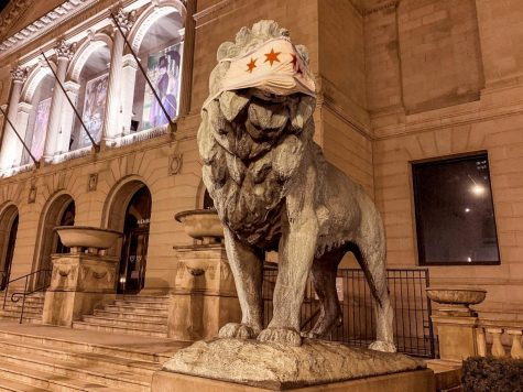 A lion statue with a mask placed on it at the Art Institute of Chicago.