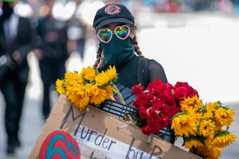 A masked protester holds a sign and flowers.