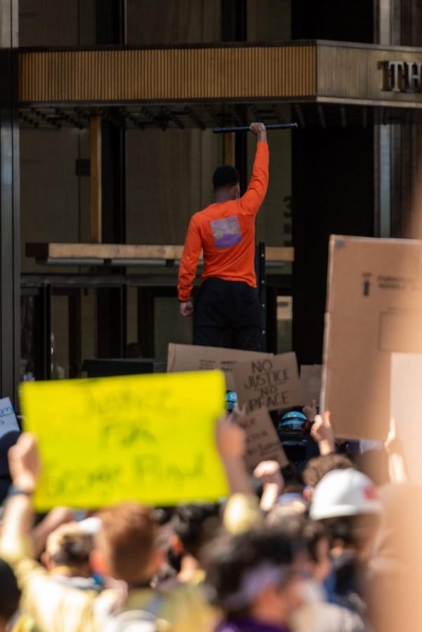 A protester stands above the crowd.