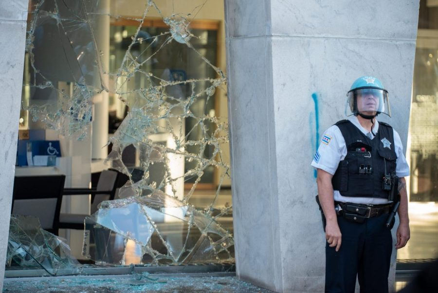An officer stands by a large window broken during the protest.