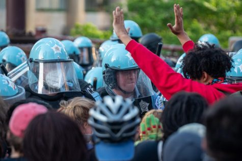 FILE-Officers attempt to block protesters, including one with their hands up.