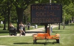 A sign along the bluff in downtown St. Joseph, Mich., encourages social distancing Tuesday, June 2, 2020, as the state slowly continues to open after being shut down for months due to the COVID-19 pandemic.(Don Campbell/The Herald-Palladium via AP)