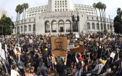 In this photo taken with a wide angle lens, demonstrators stand in front of Los Angeles City Hall during a protest over the death of George Floyd Tuesday, June 2, 2020, in Los Angeles. Floyd died in police custody on Memorial Day in Minneapolis.
