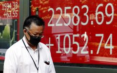 A man walks past an electronic stock board showing Japan's Nikkei 225 index at a securities firm in Tokyo, Tuesday, June 16, 2020. Asian shares have tracked a rally on Wall Street spurred by the U.S. Federal Reserve's latest promise to support markets battered by the coronavirus pandemic. Benchmarks in Japan, South Korea, Australia and China all rose in early Tuesday trading. (AP Photo/Eugene Hoshiko)