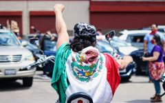 A man wears a Mexican flag on a motorcycle behind the Little Village Caravan