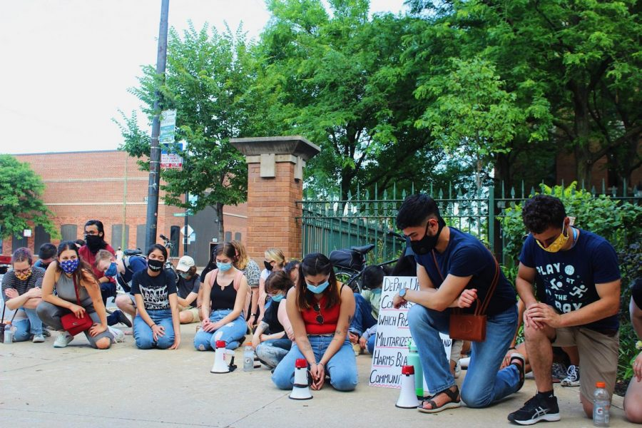 Protesters take a knee near the Lincoln Park Quad.