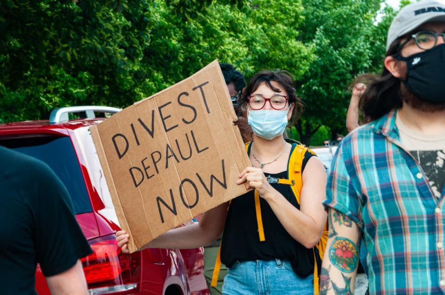 A DePaul student holds a sign at a June protest, calling for DePaul to divest from the Fraternal Order of Police
