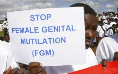 FILE - In this April 21, 2007 file photo, a Masai girl holds a protest sign during the anti-female genital mutilation (FGM) protest in Kilgoris, Kenya. The World Health Organization says the practice constitutes an