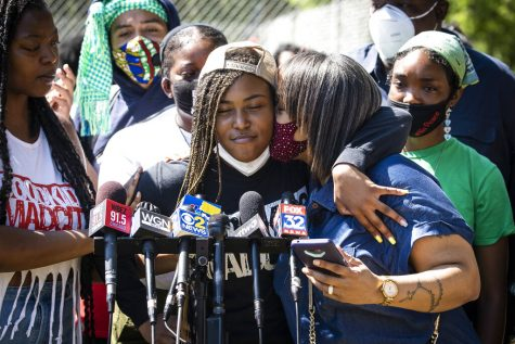 Miracle Boyd, 18, an activist with GoodKids MadCity, hugs a supporter as she speaks during a press conference in front of a statue of President George Washington near East 51st Street and South King Drive, describing a recent violent encounter she had with Chicago Police, Monday morning, July 20, 2020. Boyd was participating in a Friday evening protest against a statue of Christopher Columbus in Grant Park, when she alleges she had several teeth knocked out by a Chicago Police officer. (Ashlee Rezin Garcia/Chicago Sun-Times via AP)
