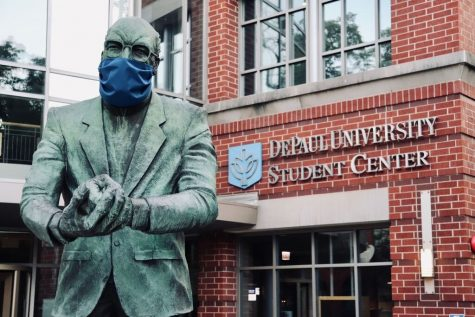 The statue of John J. Egan, located outside of the Lincoln Park Student Center, wearing a mask.