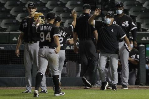 Chicago White Sox manager Rick Renteria, right, celebrates with his team after the White Sox defeated the Chicago Cubs 7-3 in an exhibition baseball game at Wrigley Field in Chicago, Sunday, July 19, 2020.