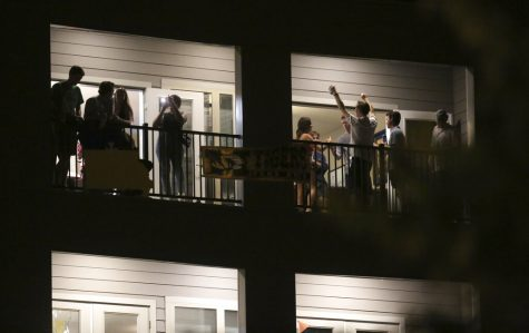 Partiers congregate on the balcony of a downtown apartment on Tuesday, Sept. 1, 2020, in Columbia, Mo., near the University of Missouri campus. Many colleges quickly scrapped in-person learning in favor of online after cases began to spike, bars have been shut down in college towns, and students, fraternities and sororities have been repeatedly disciplined for parties and large gatherings. (Dan Shular/Missourian via AP)