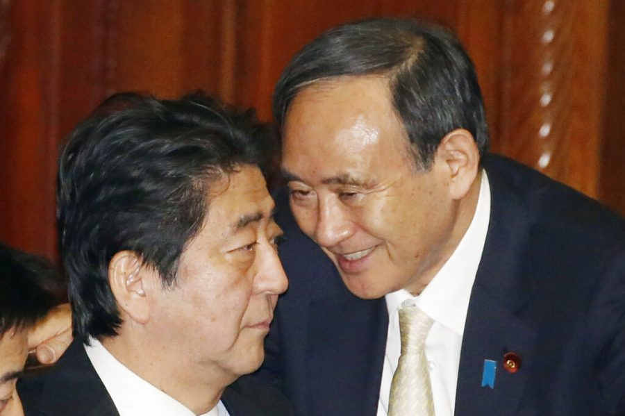 Then Prime Minister Shinzo Abe, left, and then Chief Cabinet Secretary Yoshihide Suga talk at a plenary session of the parliament's Lower House in Tokyo in December, 2016. Japan's Parliament elected Suga as prime minister Wednesday, Sept. 16, 2020, replacing long-serving leader Abe with his right-hand man. (Kyodo News via AP)