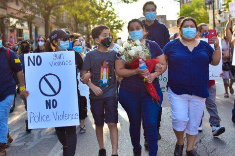 La madre de Miguel, María Vega, llevó un ramo de rosas blancas mientras la familia marchaba. // Miguel's mother, Maria Vega, carries a bouquet of white rosas while the family leads the march.