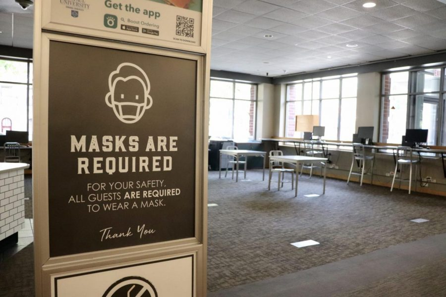 Brownstones Coffee, located in the Lincoln Park Student Center, with social distance seating and sign reminding students to wear face covering.