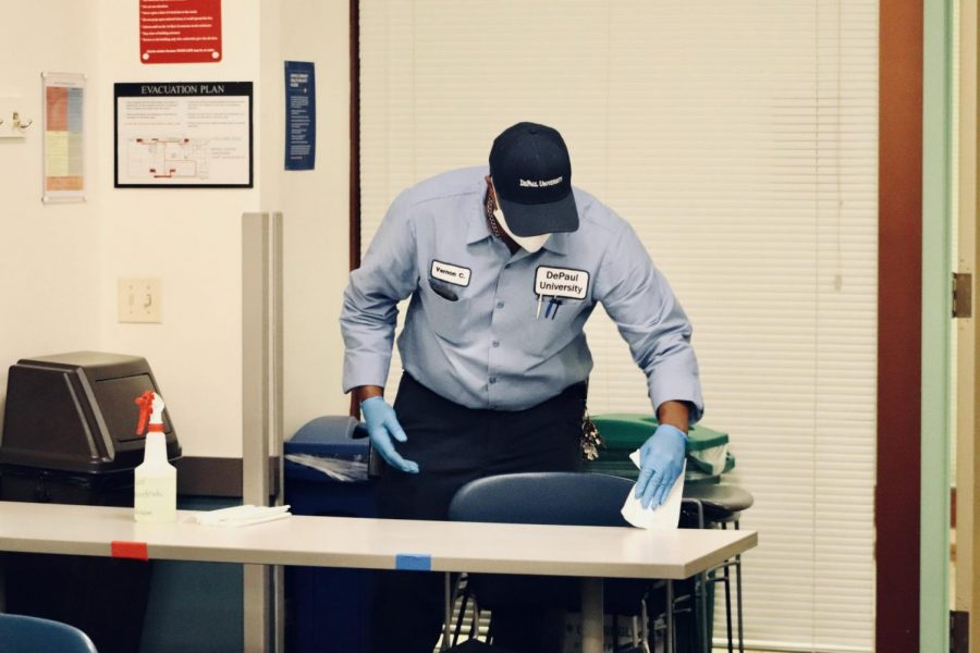 A Facility Operations employee disinfects a classroom as part of new regulations designed to prevent the spread of COVID-19.