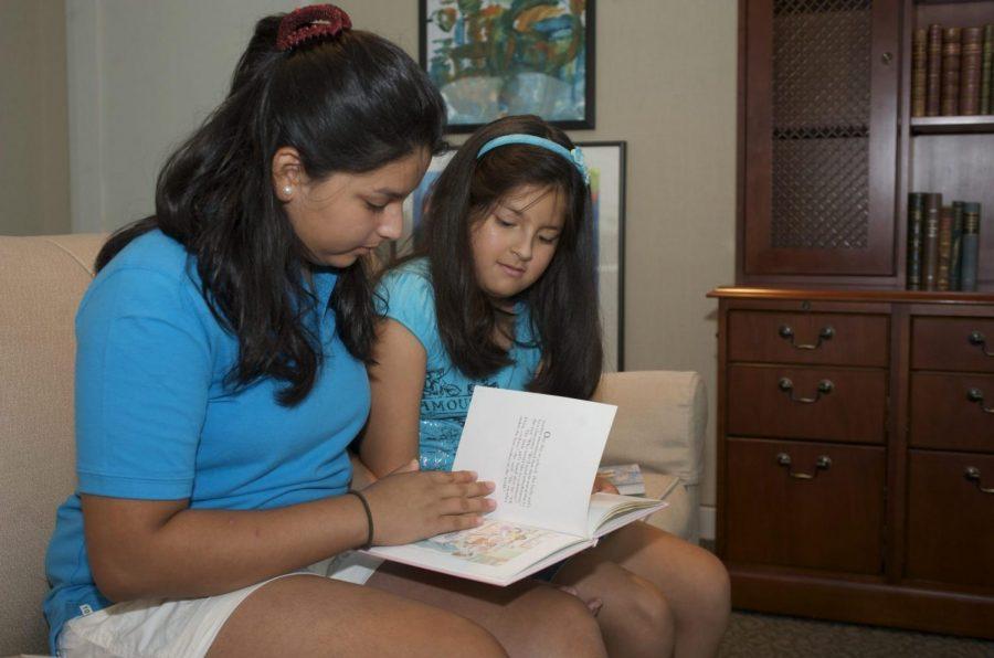 Una madre voltea las páginas de un libro con su hija.
