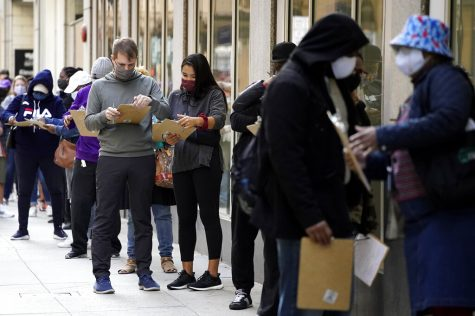 People wait line to early vote as they fill out voter registration cards outside the Loop Super Site in downtown Chicago, Sunday, Oct. 11, 2020. It is the only location allowing early voting in the city right now, but early voting will expand to locations in all 50 wards on Oct. 14. (AP Photo/Nam Y. Huh)
