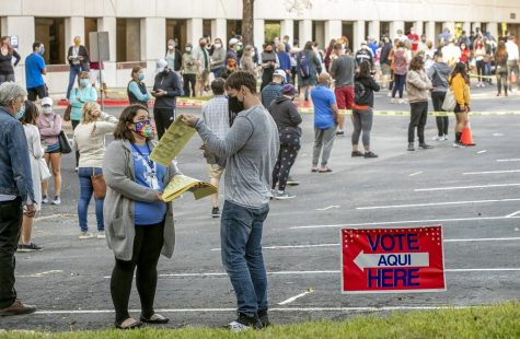 People wait in a long line to cast ballots for the general election at an early voting location at the Renaissance Austin Hotel on Tuesday, Oct. 13, 2020, in Austin, Texas. (Jay Janner/Austin American-Statesman via AP)