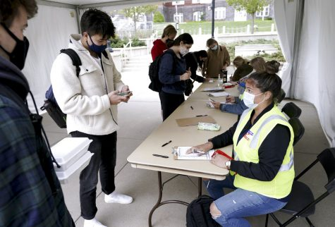 FILE-Elizabeth Quirmbach, right, registers Ayuka Sinanoglu, center, a Sophomore at the UW on Wednesday, Oct. 19, 2020  outside of the UW Memorial Union in Madison, Wis.  A small but steady stream of masked UW-Madison students stopped by voter registration tables outside the unions last week to perform their civic duty. Madison City Clerk's office employees helped them through the paperwork, sanitized their used pens and talked among themselves as they waited for the next students to filter into the fairly empty tents.(Steve Apps/Wisconsin State Journal via AP)