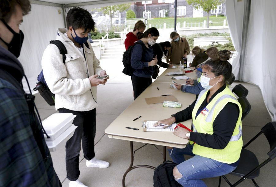 Elizabeth Quirmbach, right, registers Ayuka Sinanoglu, center, a Sophomore at the UW on Wednesday, Oct. 19, 2020  outside of the UW Memorial Union in Madison, Wis.  A small but steady stream of masked UW-Madison students stopped by voter registration tables outside the unions last week to perform their civic duty. Madison City Clerk's office employees helped them through the paperwork, sanitized their used pens and talked among themselves as they waited for the next students to filter into the fairly empty tents.(Steve Apps/Wisconsin State Journal via AP)
