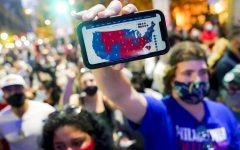 A supporter of President-elect Joe Biden holds up his mobile phone to display the electoral college map outside the Philadelphia Convention Center after the 2020 Presidential Election is called, Saturday, Nov. 7, 2020, in Philadelphia. (AP Photo/John Minchillo)