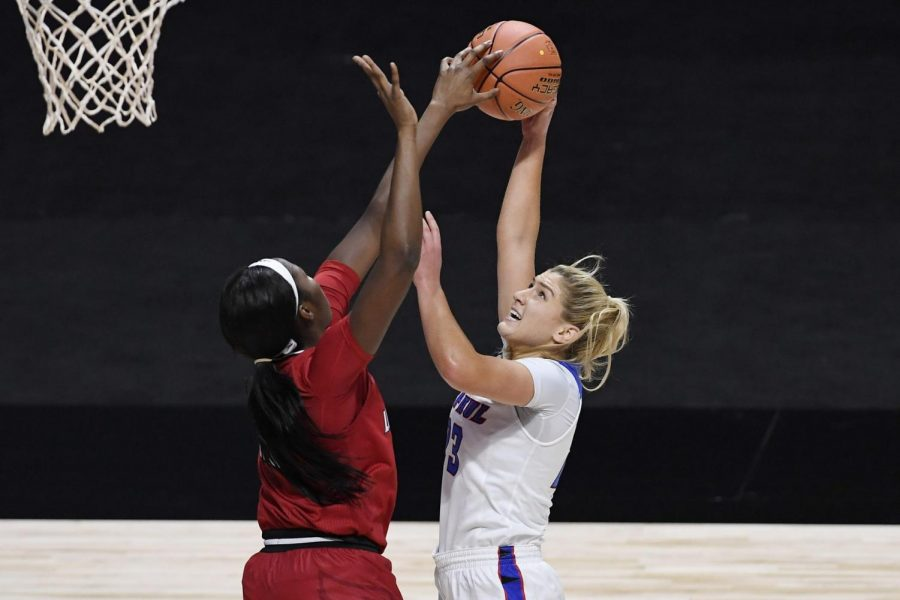 Louisville's Elizabeth Dixon, left, stops a shot-attempt by DePaul's Dee Bekelja in the first half of an NCAA college basketball game, Friday, Dec. 4, 2020, in Uncasville, Conn.
