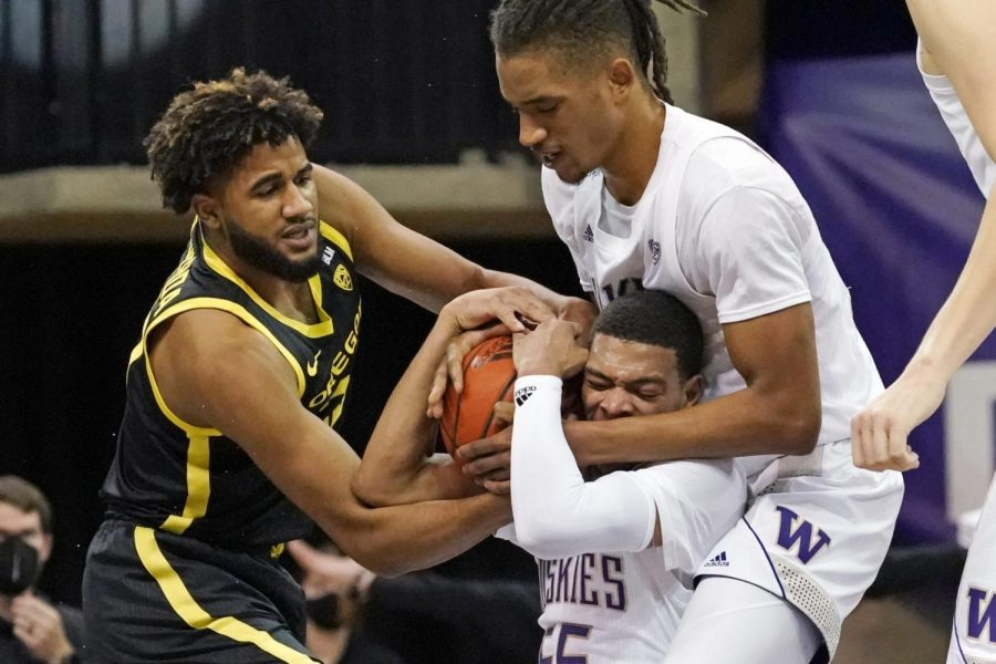 : Oregon's LJ Figueroa, left, struggles for control of the ball with Washington's Quade Green, bottom right, and Hameir Wright during the first half of an NCAA college basketball game Saturday, Dec. 12, 2020, in Seattle.
