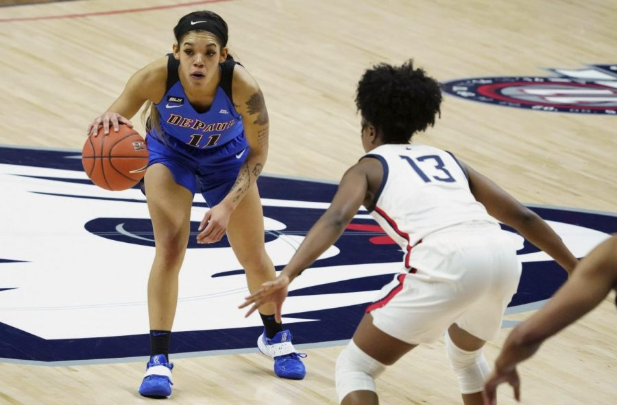 DePaul guard Sonya Morris (11) is defended by Connecticut guard Christyn Williams (13) during the first half of an NCAA college basketball game Tuesday, Dec. 29, 2020, in Storrs, Conn