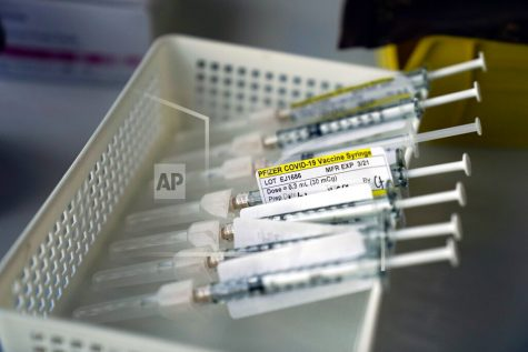 FILE - In this Jan. 7, 2021, file photo syringes containing the Pfizer-BioNTech COVID-19 vaccine sit in a tray in a vaccination room at St. Joseph Hospital in Orange, Calif. Taking a new direction to speed release of coronavirus vaccines, President-elect Joe Biden