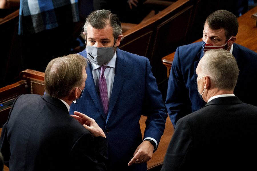 Sen. Ted Cruz, R-Texas, talks with others as a joint session of the House and Senate convenes to confirm the Electoral College votes cast in November's election, at the Capitol in Washington, Wednesday, Jan. 6, 2021. (Erin Schaff/The New York Times via AP, Pool)