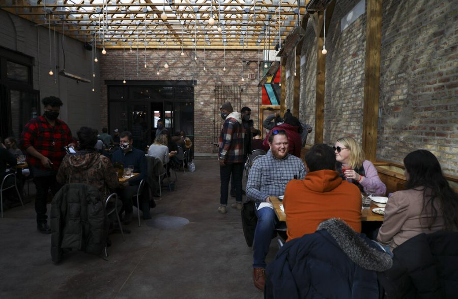Patrons enjoy drinks and lunch in the semi-open area of Pilsen Yards restaurant in Chicago after Illinois Gov. J.B. Pritzker allowed restaurants to open for indoor dining, Saturday, Jan. 23, 2021. (Abel Uribe/Chicago Tribune via AP)