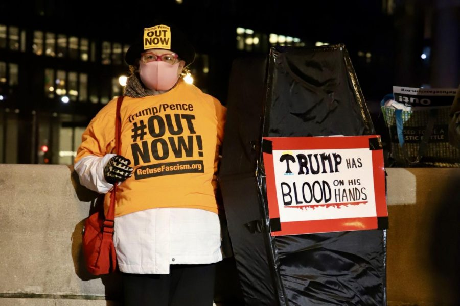 Sammy Lines, a member of Refuse Fascism Chicago, stands beside a  coffin with messages criticizing the President Trump.