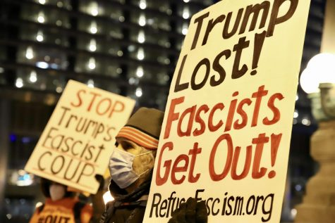 Signs targeting President Trump at a gathering outside Trump Tower held by Refuse Fascism.