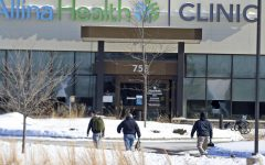 In this Tuesday, Feb. 9, 2021 file photo, law enforcement personnel walk toward the Allina Health clinic where multiple people were shot in Buffalo, Minn. Doctors say they're facing increasing threats of violence for refusing to prescribe opioids or trying to wean patients off the addictive painkillers. The issue was underscored by Tuesday's shooting at the Minnesota clinic.