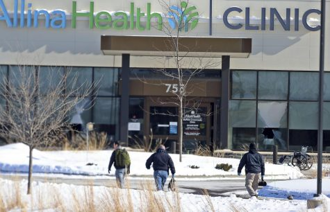 In this Tuesday, Feb. 9, 2021 file photo, law enforcement personnel walk toward the Allina Health clinic where multiple people were shot in Buffalo, Minn. Doctors say they