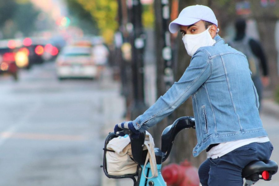 A man in Wicker Park sporting a mask while riding a divvy bike.