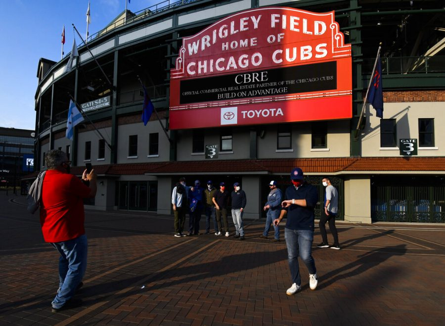 FILE - Chicago Cubs fans stand outside of Wrigley Field before a baseball game against the Minnesota Twins in Chicago, in this Sunday, Sept. 20, 2020, file photo. Thousands of fans of the Chicago Cubs and the Chicago White Sox will get to see their teams play in person this season, Mayor Lori Lightfoot announced on Monday, March 9, 2021. In a news release, Lightfoot said each team will be limited to 20% capacity. (AP Photo/Matt Marton, File)