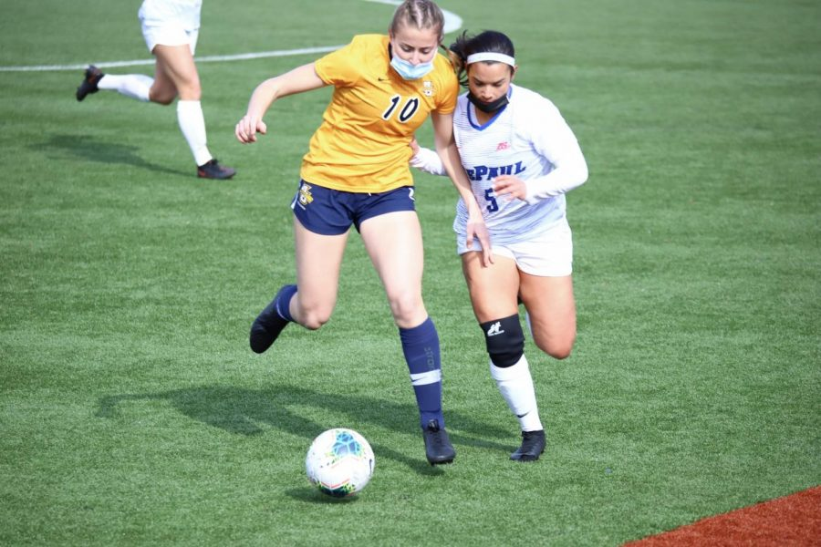 DePaul redshirt senior defender Adrian Walker goes for the ball against a Marquette defender on March 7 at Wish Field.