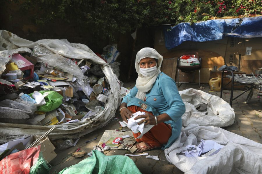 Manuwara Begun, 46, sorts out garbage collected from households in New Delhi, India, Tuesday, March 9, 2021. Begun lives in a cardboard hut behind a five-star hotel in the heart of New Delhi and feels the inequity keenly. Trash pickers often find it hard to get vaccines because they are not considered by the government to be essential workers or cannot afford to wait at overburdened public hospitals for free shots. Chintan estimates that each year, those like her save the local government over $50 million and eliminate over 900,000 tons of carbon dioxide by diverting waste away from landfills. (AP Photo/Manish Swarup)