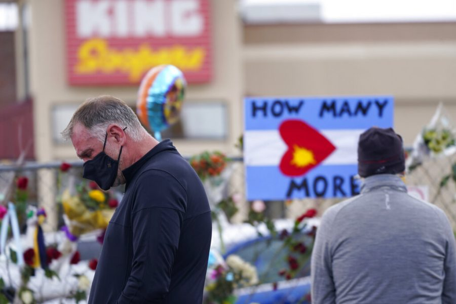 A mourner walks the temporary fence line outside the parking lot of a King Soopers grocery store,  Friday, March 26, 2021, in Boulder, Colo., the site of a mass shooting in which 10 people died earlier in the week. (AP Photo/David Zalubowski)
